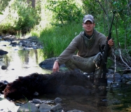 Canyon Young with the Black Bear he harvested during the August hunt in northern NM.