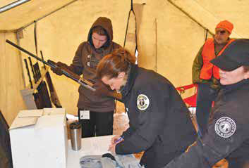 Jennifer Morgan, the NMDGF Hunter Education Program coordinator (center) and Jessica Fisher, the Shooting Program coordinator (right) check out shotguns to youth hunters. New Mexico Wildlife magazine, NMDGF