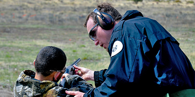 Jeremy Lane, the Game and Fish Southwest Area public information officer, assists a young hunter education participant on the proper stance and handling of a shotgun prior to shooting it during a hunter education camp at Philmont Scout Ranch. Photo by Ross Morgan, New Mexico Wildlife magazine, NMDGF.