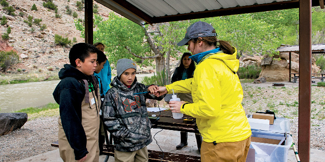 (right to left) Christy Wall with the New Mexico Wildlife Center works with Cruz Sandoval and Loren Vigil to test water samples pulled from the Rio Chama. The students were asked later what might influence water turbidity, temperature and pH levels. Photo by Zen Mocarski, New Mexico Wildlife magazine, NMDGF.