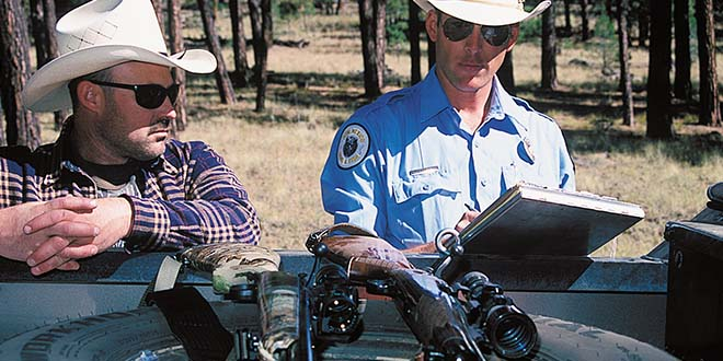 Dan Brooks, Law Enforcement Chief, watches Sgt. Chris Neary fill out evidence tags. Photo: Martin Frentzel. New Mexico Wildlife Magazine, Vol-49, Num-1 Spring 2004. (Making Tracks: A Century of Wildlife Management. (History of the New Mexico Department of Game and Fish).