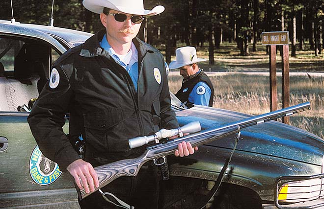 Officer Shawn Denny with rifle taken for evidence. Photo: Martin Frentzel. New Mexico Wildlife magazine, Vol-49, Num-1 Spring 2004 NMDGF. (Making Tracks: A Century of Wildlife Management. (History of the New Mexico Department of Game and Fish).
