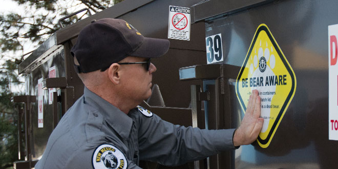 "Bob Osborn, assistant chief of private land programs for the New Mexico Department of Game and Fish, affixes a ""Be Bear Aware"" sticker to one of the new bear-resistant dumpsters installed at the Los Alamos Medical Center. NMDGF photo by Zen Mocarski, New Mexico Wildlife magazine Spring 2017 Vol60, Num1, New Mexico Department of Game and Fish."