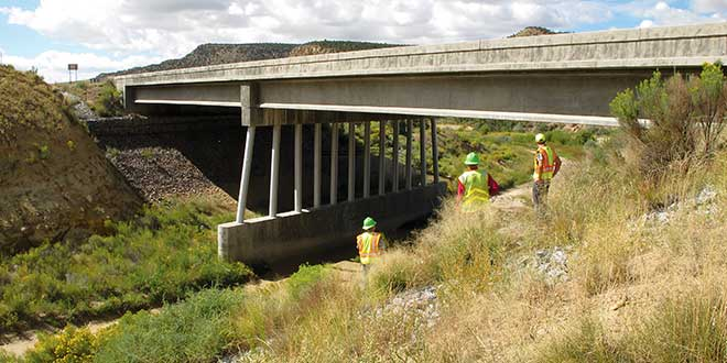 NMDOT employees inspect one of two large bridges over the Rio Puerco on U.S. Highway 550 south of Cuba, a high wildlife-vehicle collision hotspot. Eight-foot tall woven wire fencing constructed along the highway right-of-way will force wildlife to move under the highway at these two bridge locations. Department photo by Mark Watson.